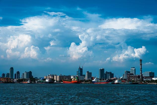 ภาพหมู่ตึกริมฝั่งแม่น้ำเจ้าพระยา และมีท้องฟ้า ที่เต็มไปด้วยเมฆสีขาวก้อนโตลอยอยู่เหนือตึกนั้น
