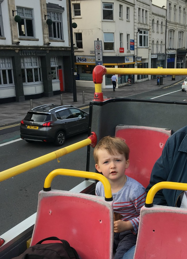 Boy-sitting-on-top-deck-of-open-air-bus-in-Cardiff