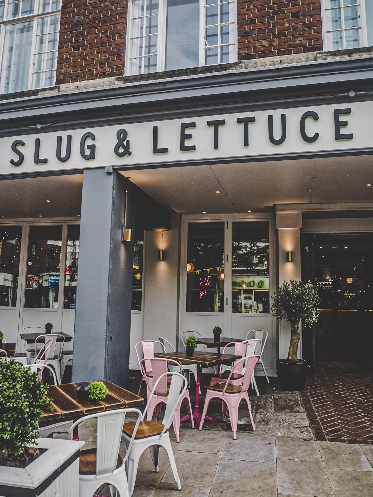 The store front of the new Slug & Lettuce location in Watford with pink and white outdoor seating and green fake plants