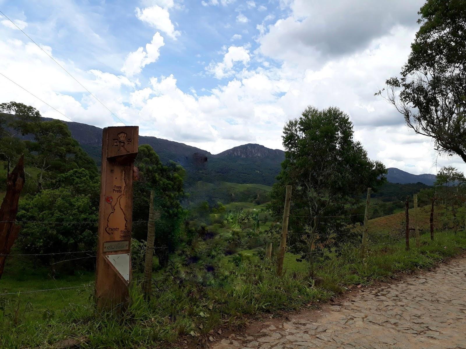 Estrada entre Bichinho e Tiradentes com o marco da estrada real e a serra
