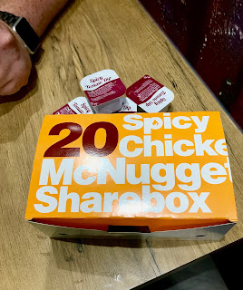 A rectangular yellow box with 20 in dark red font with Spicy Chicken McNuggets Sharebox in white font on a white rectangular table on a bright background