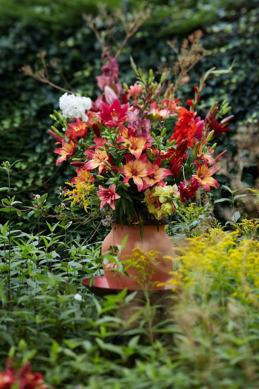 Jarrón con flores de azucena (Lilium) en el jardín