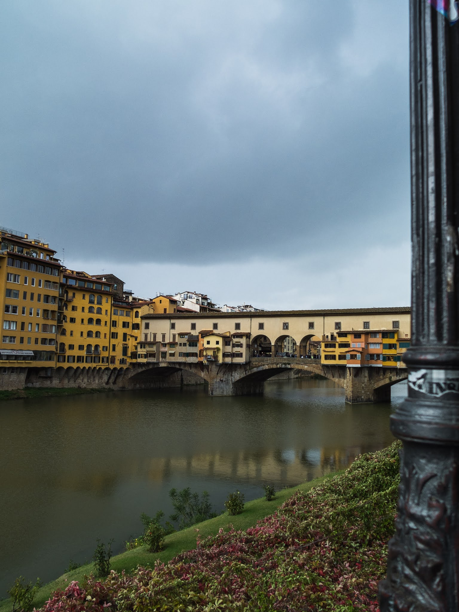 View of Ponte Vecchio with the embankment and a street light post to the right.