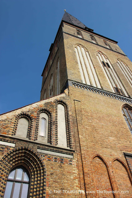 Tower and facade of a red brick church.
