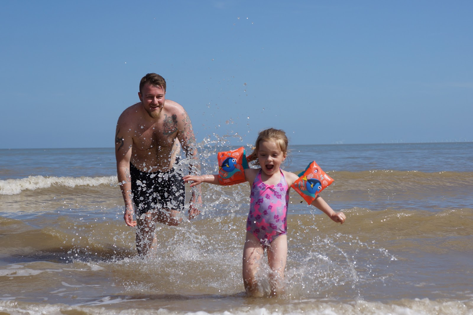 dad and daughter splashing in the sea