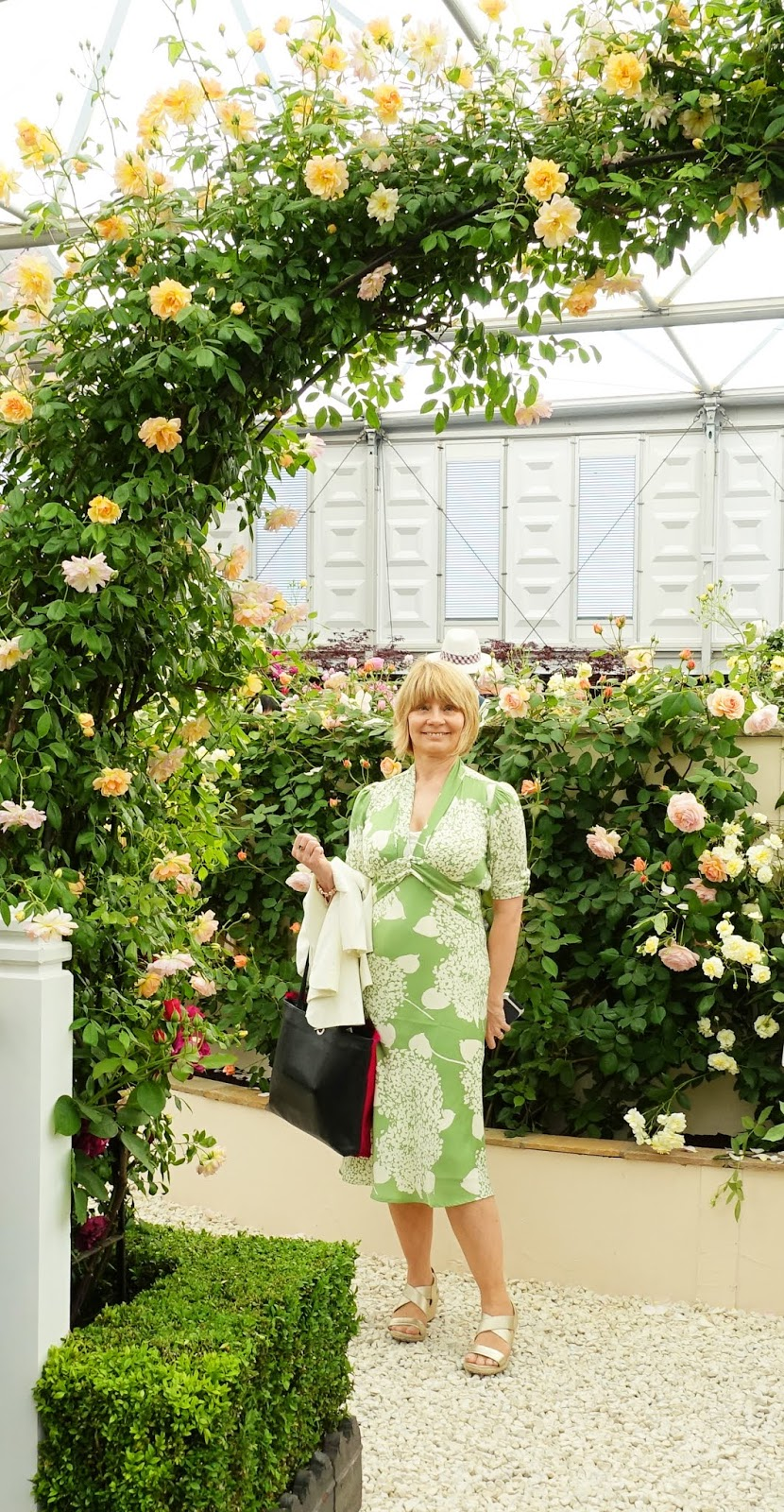 The magnificent rose arch welcoming visitors to the David Austin Roses stand at the Chelsea Flower Show, with Gail Hanlon in green floral dress