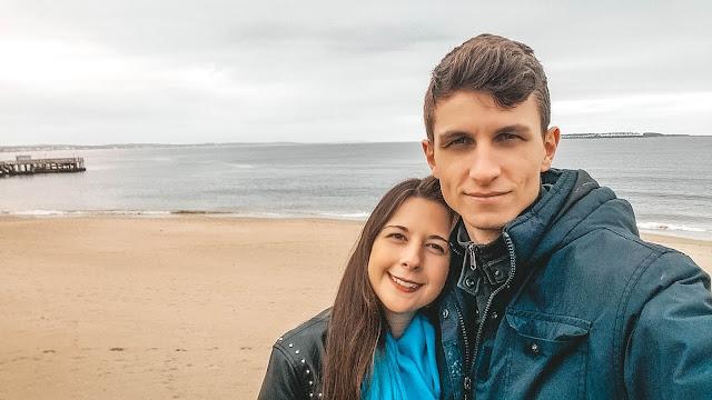 Casal tirando selfie em frente a praia
