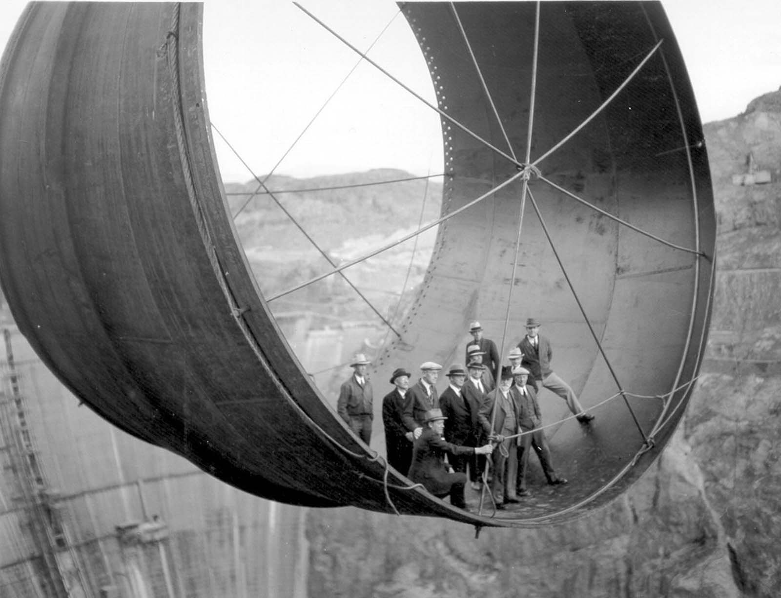 Officials ride in one of the penstock pipes of the soon-to-be-completed Hoover Dam. 1935.