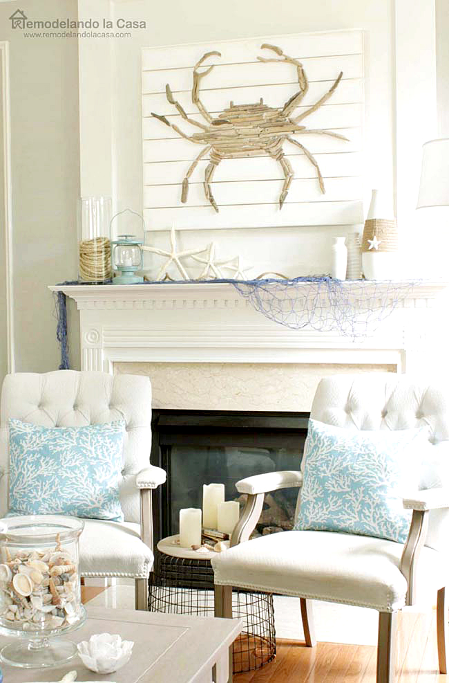 blue alga pillows on white chairs, sea shells on vase, summer mantel candles