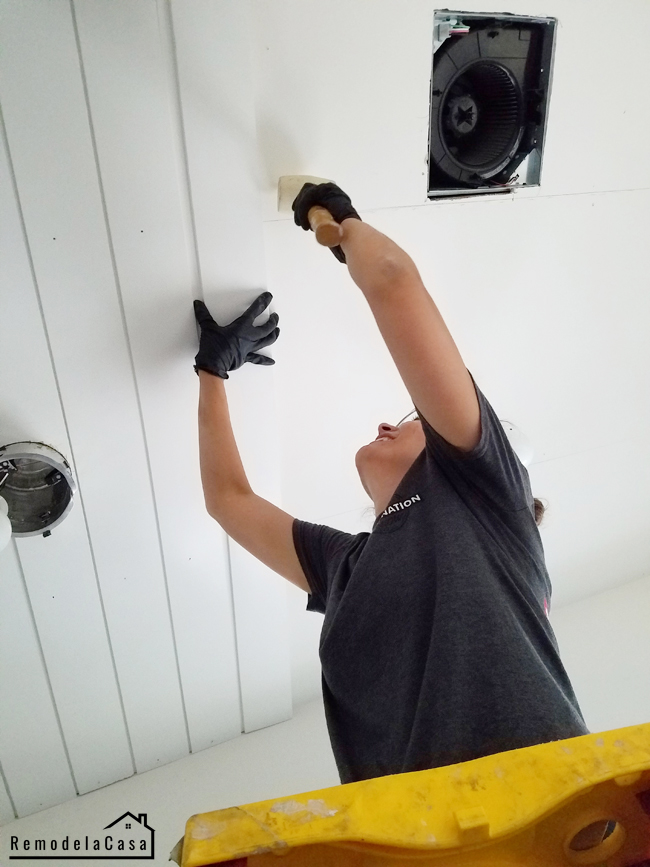 Cristina Garay installing planked ceiling in bathroom.