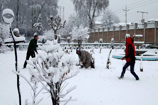 Tourist play with snow at a park during heavy snowfall in Srinagar