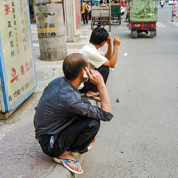 Men sitting on their haunches in Asia