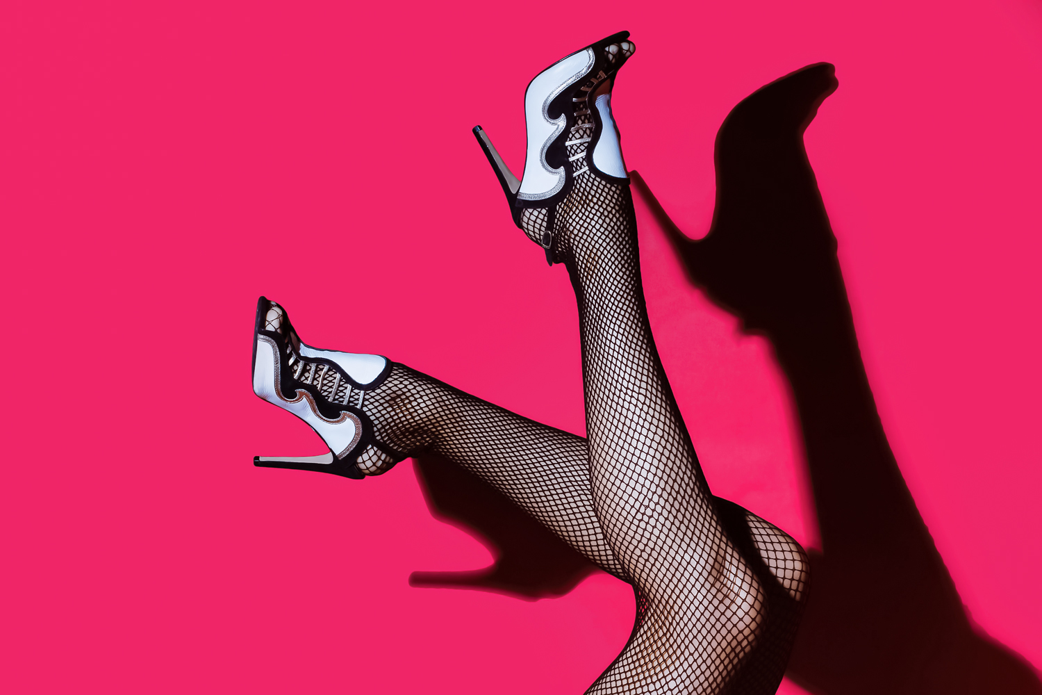 a close up picture of legs wearing fishnet pantyhose and heels