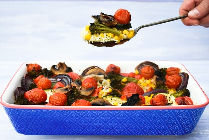 Roasted vegetable rice bake in a rectangular blue baking dish