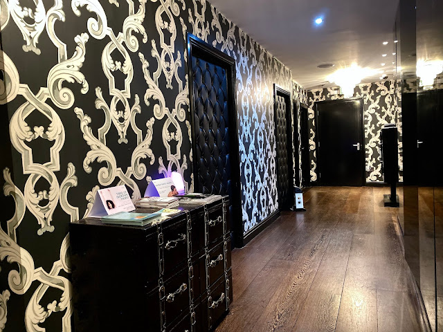 A corridor with black and white corridor and padded doors at Strip Salon Loughton