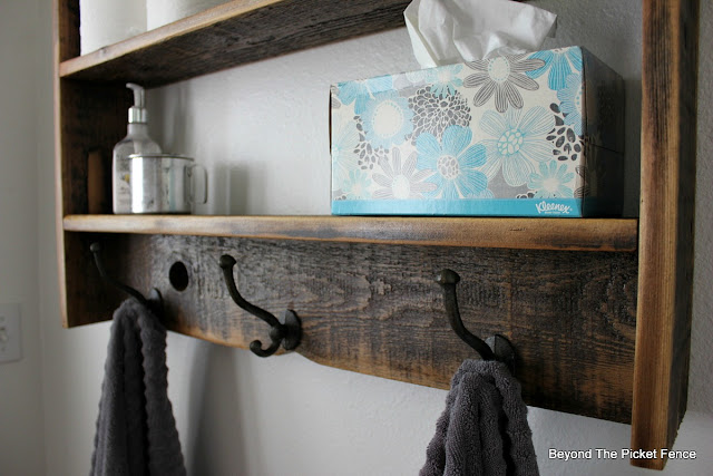 coat hooks on a rustic reclaimed wood wall shelf