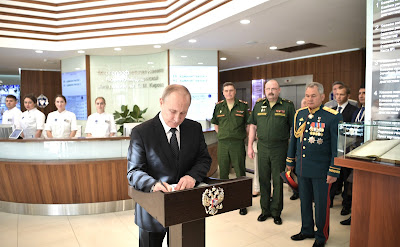 Vladimir Putin signs the distinguished visitors' book during his visit to the Multidisciplinary Clinic of the Kirov Military Medical Academy.