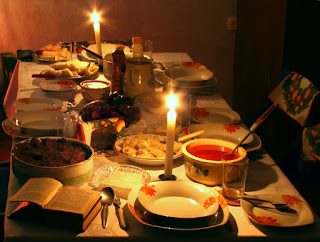 A color photo of a dinner table set with candles, white plates painted with orange flowers, and a number of unidentified foods in serving dishes.