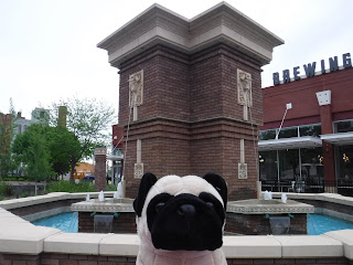 "a plush pug appears in front of an elaborate geometric fountain. the word ""brewing"" is visible on the building behind."