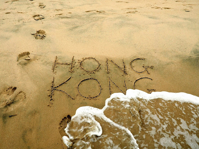 """Hong Kong"" written in the sand, with wave starting to wash it away"