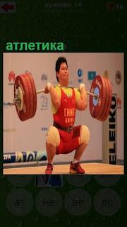 в тяжелой атлетике поднимает штангу спортсмен