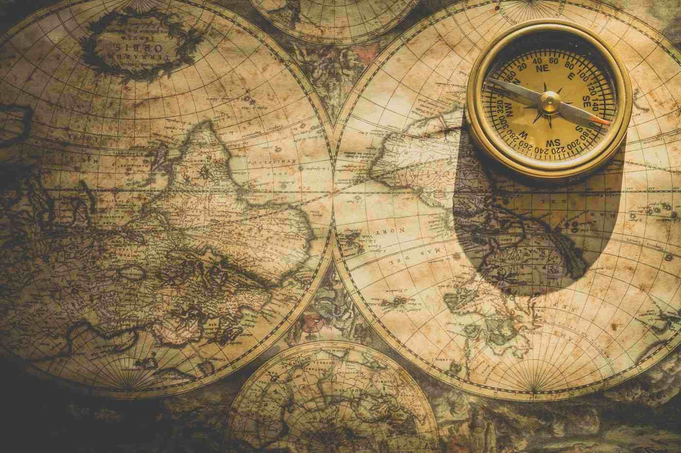map of the world with analog compass - how to have a travel adventure close to home