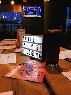 light box with letters spelling out north west blog gang on a wooden table with a pint of coke and some leaflets