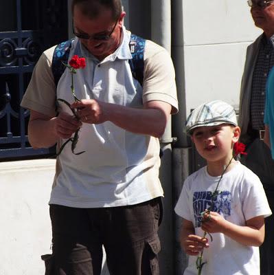 pai e filho na rua cada um segurando um cravo vermelho