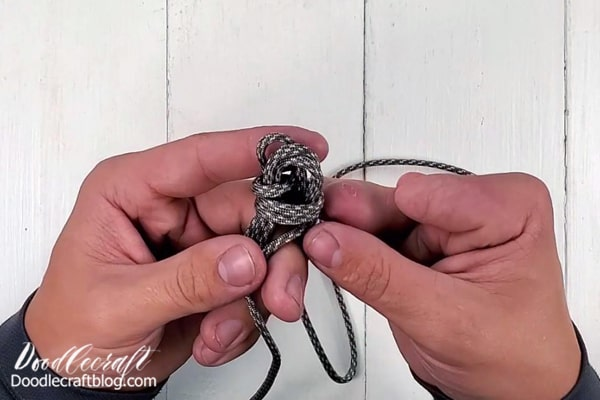 With the last loop, pull the paracord end through the center of the loops.