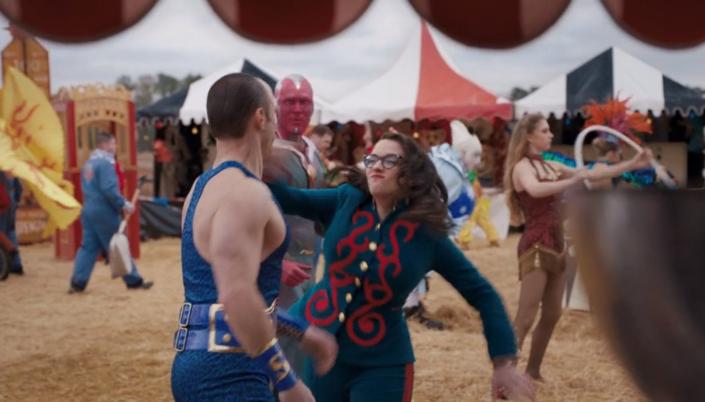 Imagem: Darcy, em uma roupa azul com detalhes vermelhos socando um agente em roupa de apresentação de circo azul, sendo observada por Visão, ao redor várias tendas de circo e pessoas em trajes de palhaços ou mímicos.