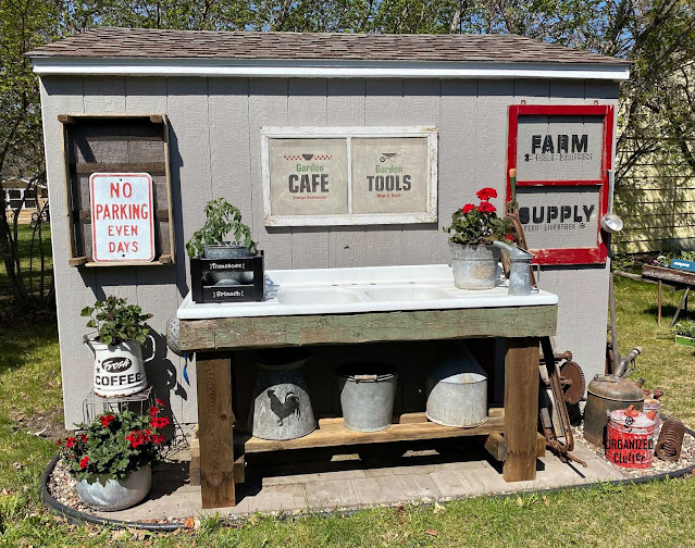 Photo of garden shed wall decorated with garden junk & red geraniums