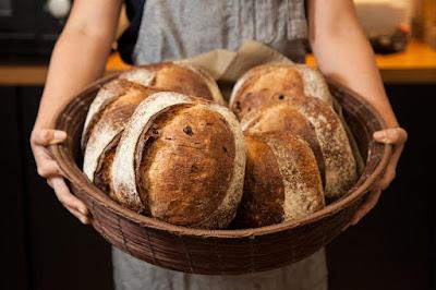 moça segurando uma cesta de pães