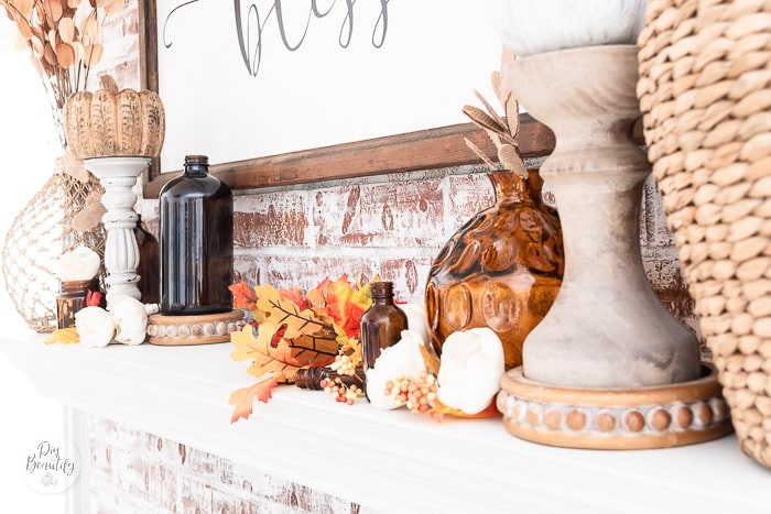 mantel with fall leaves, amber bottles, wood pumpkins and candlesticks