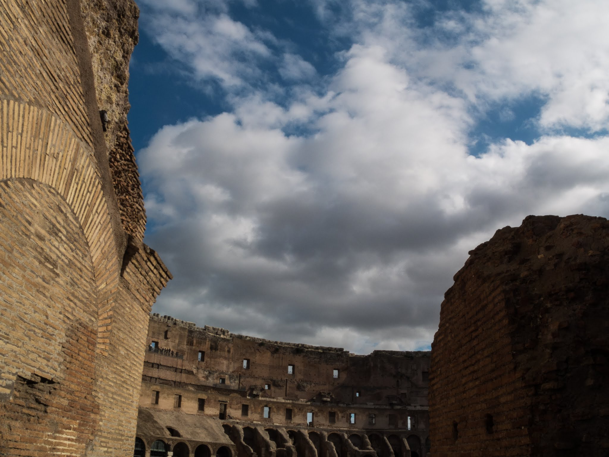 View of the inside the Colosseum from the entrance with a blue sky and clouds above.