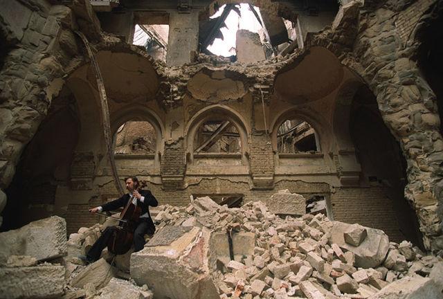 Hombre tocando el violonchelo en un edificio en ruinas