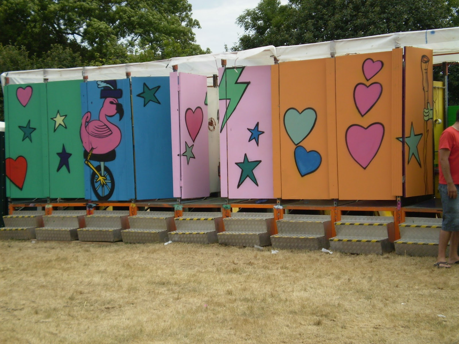 row of brightly painted compost toilets at a festival