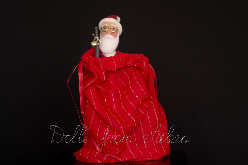 Red and gold gift bag partially open showing head of Santa Claus doll