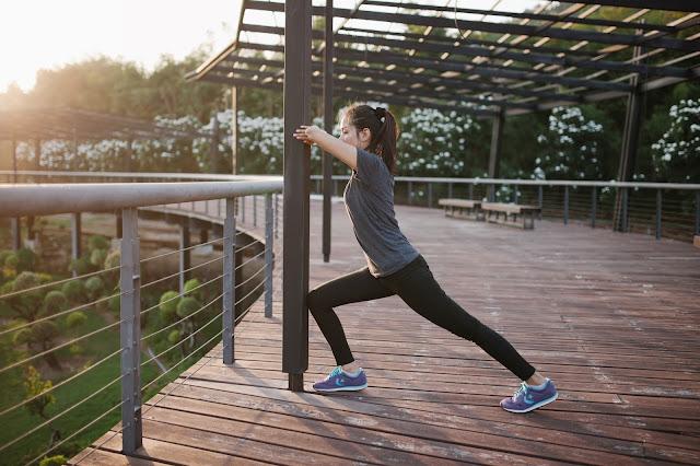 Une femme s'étire après avoir fait une séance de sport.