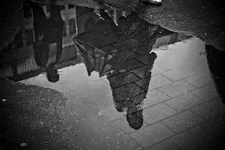 reflexo de pessoas na poça de agua