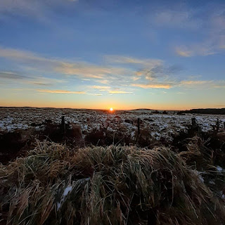 Sun rises over a snow scattered grassy expanse of moorland