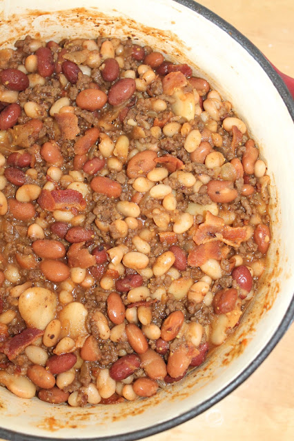 Cowboy calico beans with ground beef and bacon in a Dutch Oven.