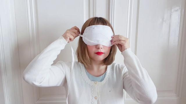 Auris bindet sich eine weiße Maske um die Augen