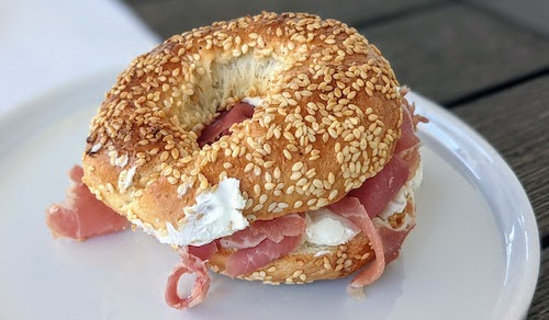 Montréal-style sesame bagel with cream cheese and prosciutto
