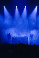 DJ behind the decks, lit in blue spotlights