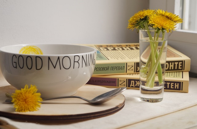 good morning bowl on table with yellow flowers and books