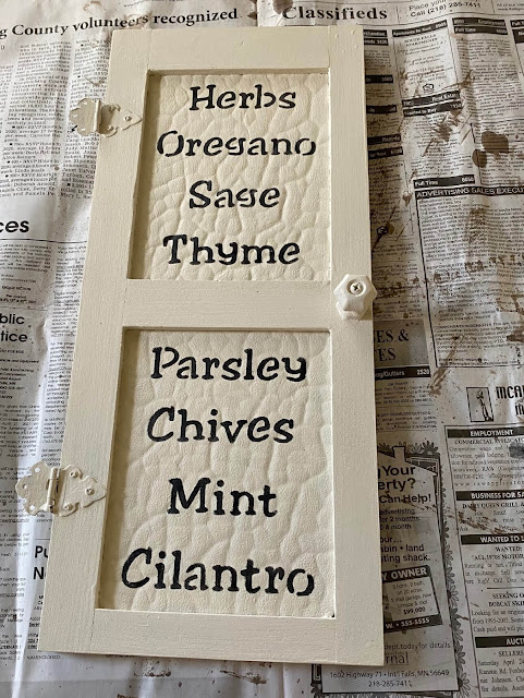 Photo of herb names stenciled on a small wall decor door