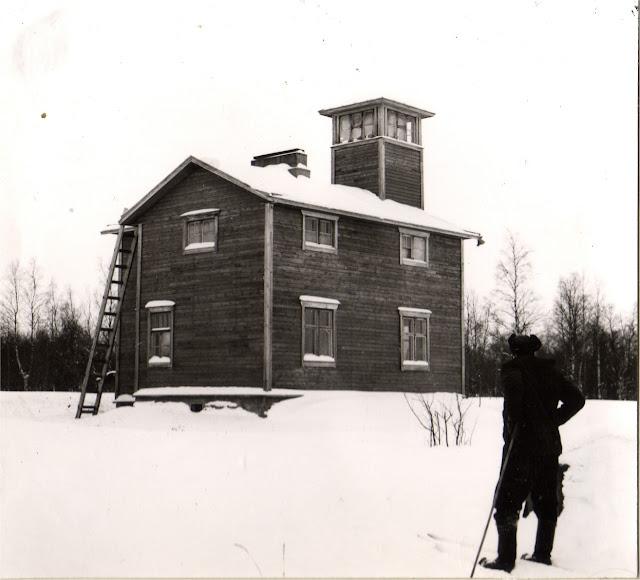 Luotsiasema talvella. Etualalla seisoo mies karvalakkipäässä ja sukset jalassa.