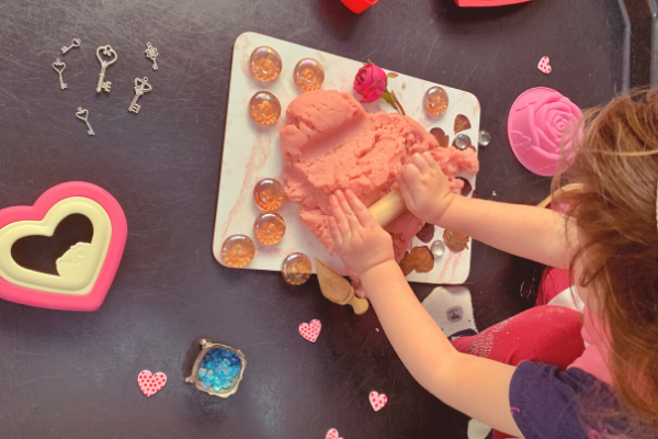 Rolling dough on the Valentine's Day sensory rose playdough tuff tray activity