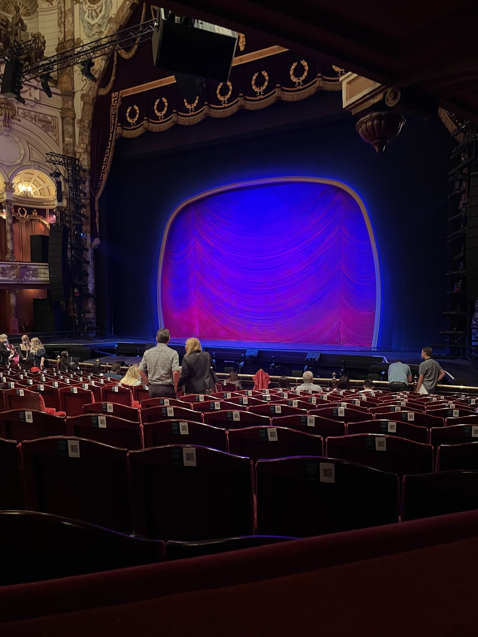 The view from stalls box G at the London Coliseum. The stage is lit up purple and are a few people taking their seats.