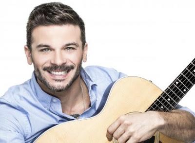 Foto de Pedro Capó abrazando su guitarra